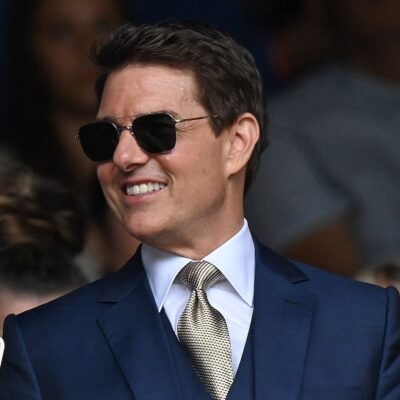 Tom Cruise smiling in a blue suit and black sunglasses