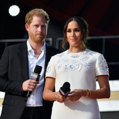 Prince Harry in a black suit with Meghan Markle in a white dress on stage