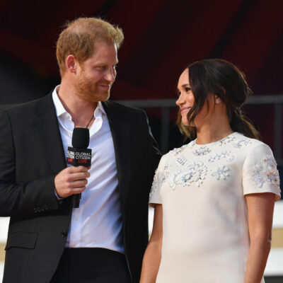 Prince Harry in a black suit smiling with Meghan Markle in a white dress