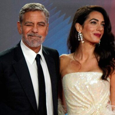George Clooney winking in a black suit with Amal Clooney in a white dress