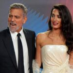George Clooney in a black suit with Amal in a white dress