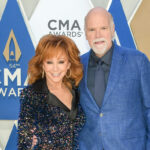 Reba McEntire smiling in a black dress with Rex Linn in a blue suit