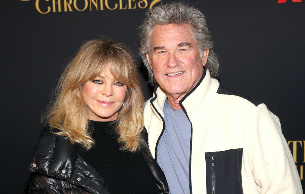 Kurt Russell in a white jacket smiling with Goldie Hawn in a black jacket