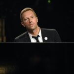 Chris Martin in a black suit playing piano on stage