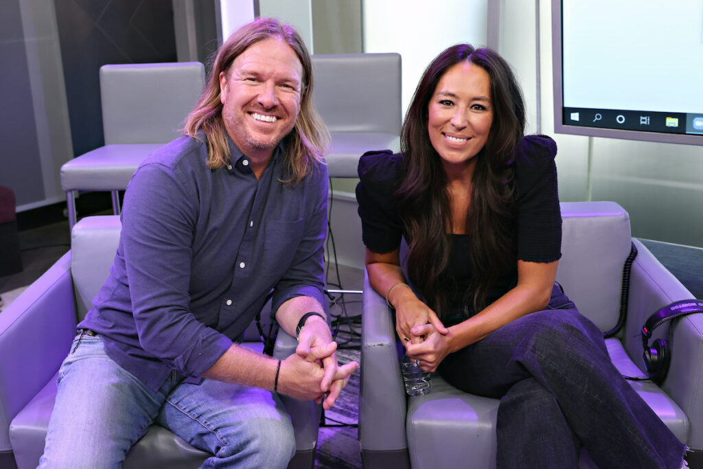 Chip and Joanna Gaines smiling while sitting in chairs