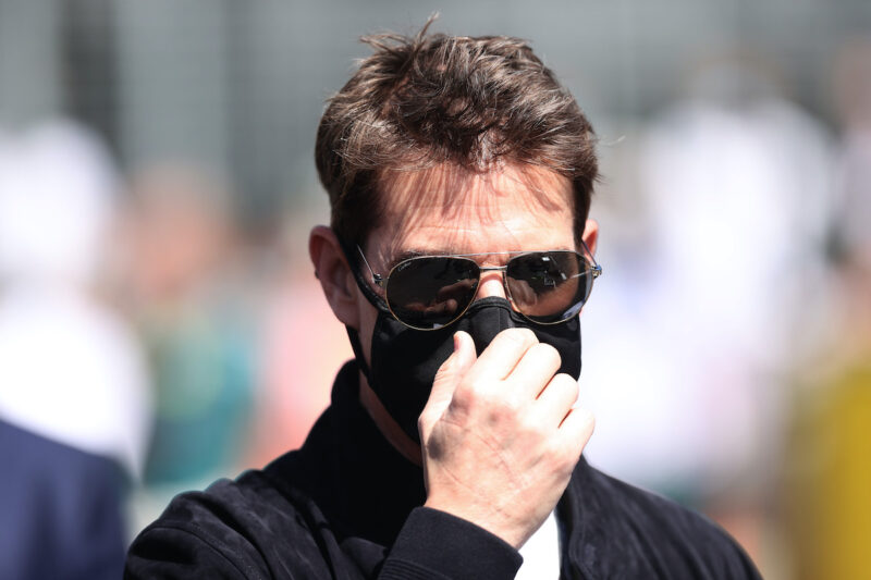 Tom Cruise in a black jacket, facemask, and sunglasses