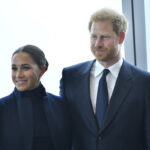 Meghan Markle in a navy jacket with Prince Harry in a navy suit
