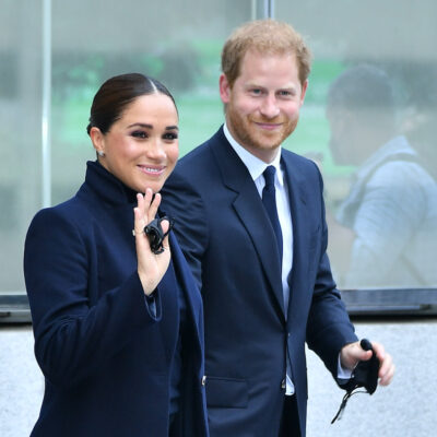 Prince Harry in a blue suit with Meghan Markle waving in a blue coat