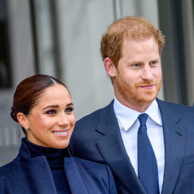 Meghan Markle in a blue suit smiling with Prince Harry in a blue suit