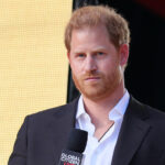Prince harry in a black suit with a microphone