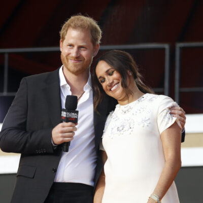 Prince Harry in a suit hugging Meghan Markle in a white dress