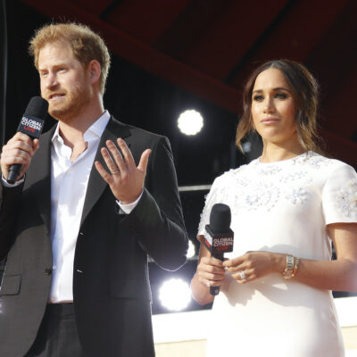 Prince Harry in a black suit speaking with Meghan Markle in a white dress