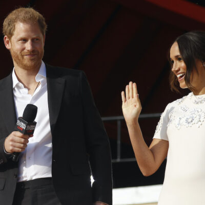 Prince Harry in a black suit and Meghan Markle in a white dress