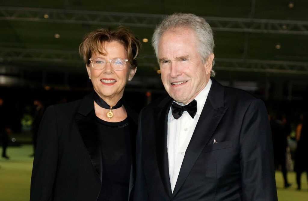Warren Beatty in a tuxedo with wife Annette Bening in a black outfit