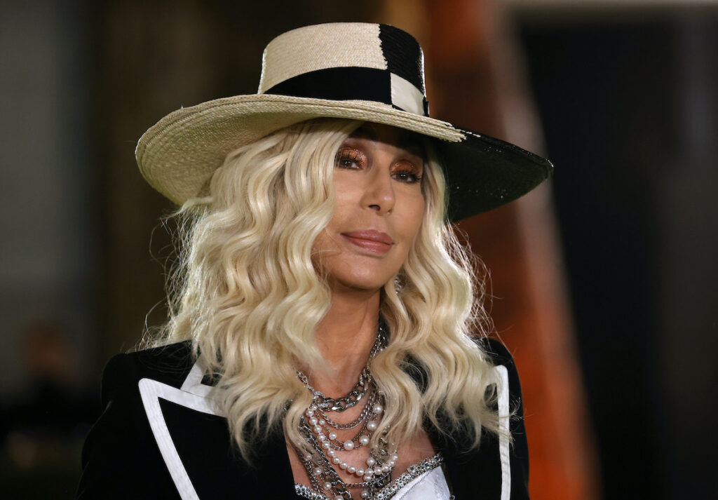 Cher in a black jacket and hat