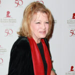 Angie Dickinson in a black coat and red scarf