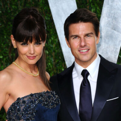 Katie Holmes in a blue dress with. Tom Cruise in a suit in 2012