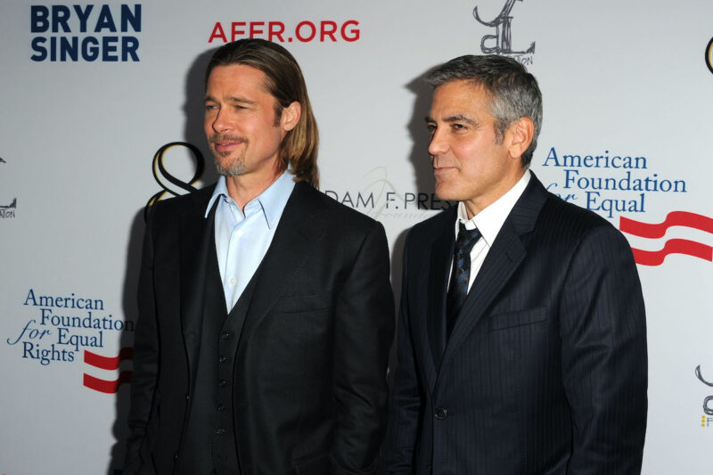 Brad Pitt in a black suit with George Clooney in a charcoal suit