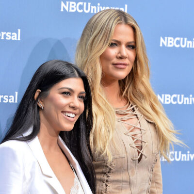 Kourtney Kardashian in a white jacket with Khloe Kardashian in a tan top