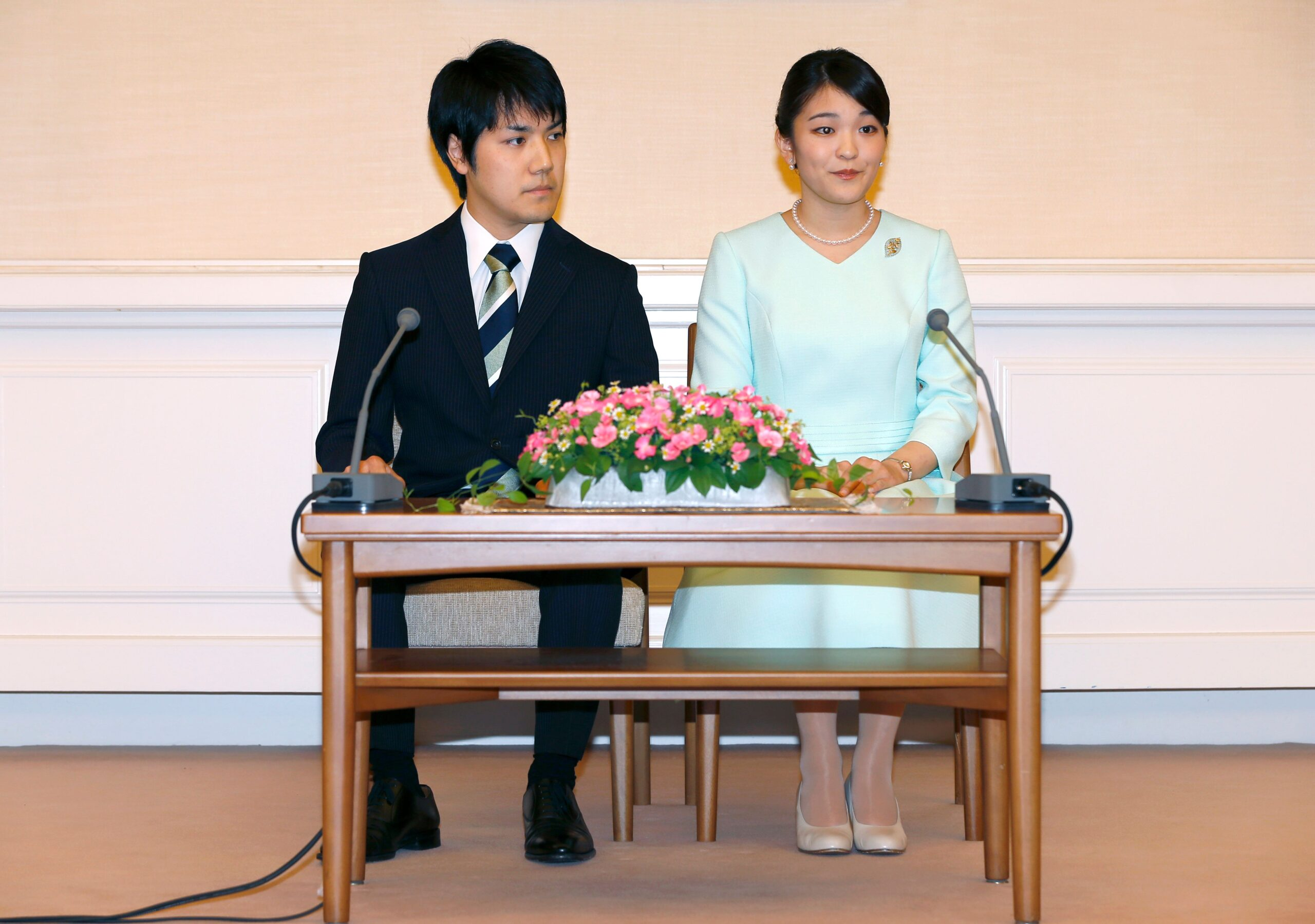Kei Komuro on the left, Princess Mako on the right, sitting a small table announcing their engagement.