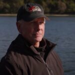 Mark Harmon in a brown jacket and black hat in a river