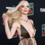 Anya Taylor-Joy flips her hair back while wearing a gold dress on the red carpet