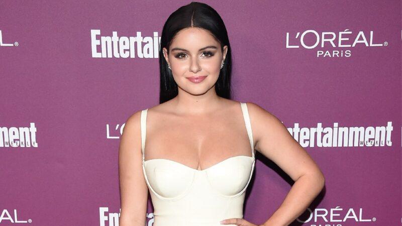 Ariel Winter wears a white dress against a purple background
