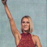 Celine Dion with her right arm raised triumphantly.