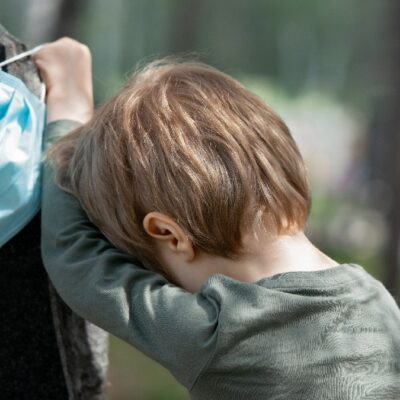 A small boy in a green shirt holds a face mask while leaning sadly on a black gravestone