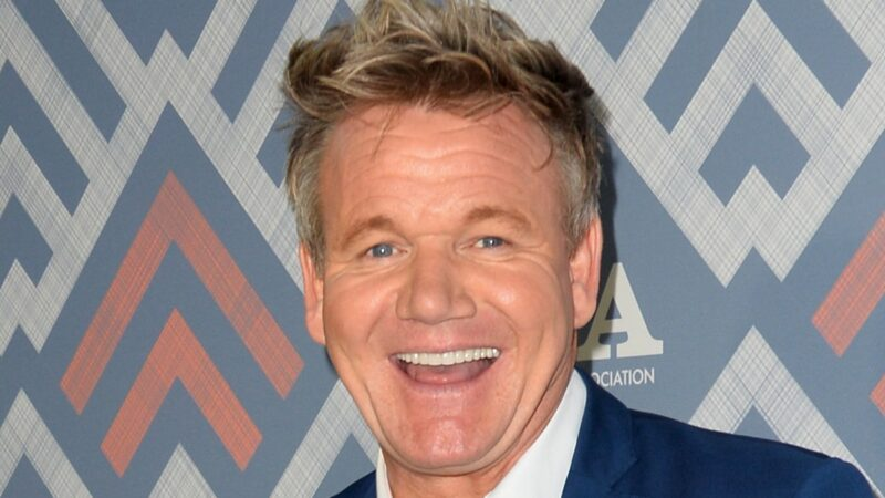 Gordon Ramsay laughs while wearing a blue suit on the red carpet