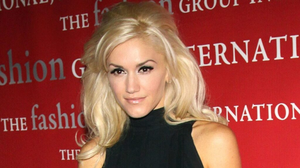 Gwen Stefani wears a black dress against a red background