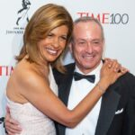 Hoda Kotb, in a white dress, stands with her arms around Joel Schiffman, in a black tux, on the red carpet