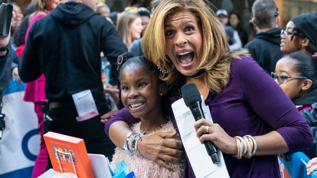 Hoda Kotb, in purple, cuddles up to a young girl while holding a microphone