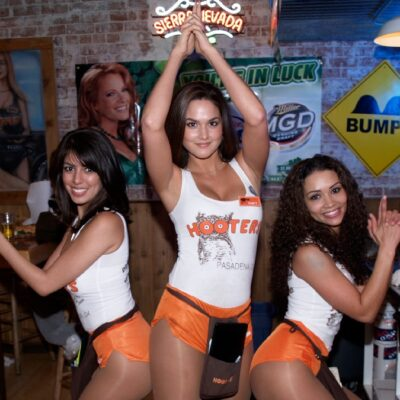 Three Hooters waitresses wearing the famous white tank top and orange shorts uniforms pose like Charlie's Angels