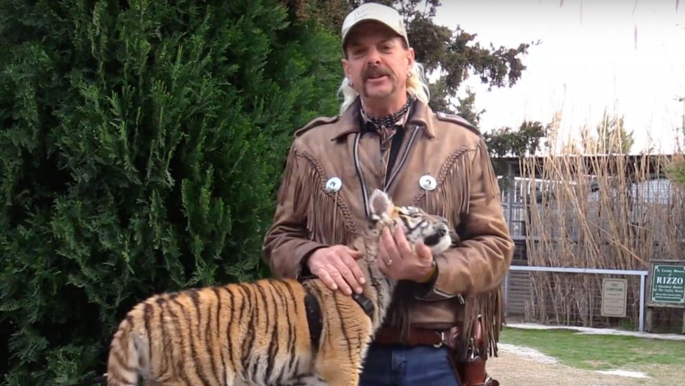 Joe Exotic holds a tiger cub closely