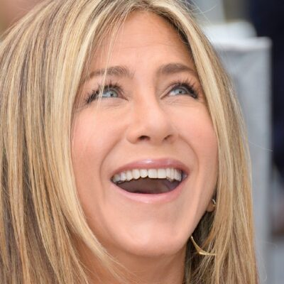 Jennifer Aniston smiles up at someone during a Hollywood Walk Of Fame ceremony