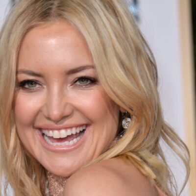 Kate Hudson looks over her shoulder and laughs on the red carpet