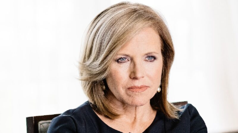 Katie Couric wears a black dress against a white background