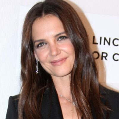 Katie Holmes wears a black suit against a white background on the red carpet