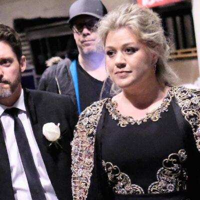 Brandon Blackstock, in a black suit, and Kelly Clarkson, in a black dress, walk together towards an awards event