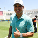 Mario Lopez in a football stadium giving a thumbs up.
