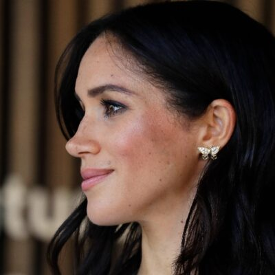 Meghan Markle looks forward as the camera catches her profile and butterfly earing