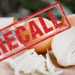 """Photo of a cut onion with the word """"recall"""" in red"""