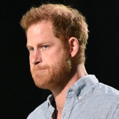 Prince Harry wears a blue shirt while making remarks onstage