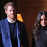 Prince Harry, in a blue suit jacket, walks with Meghan Markle, in a black top, down a hallway in Edinburgh, Scotland