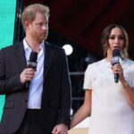 Prince Harry, in a dark suit, stands onstage with Meghan Markle, in a white dress