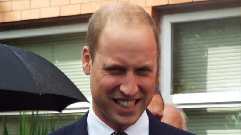 Prince William wears a dark suit and grins while walking the street
