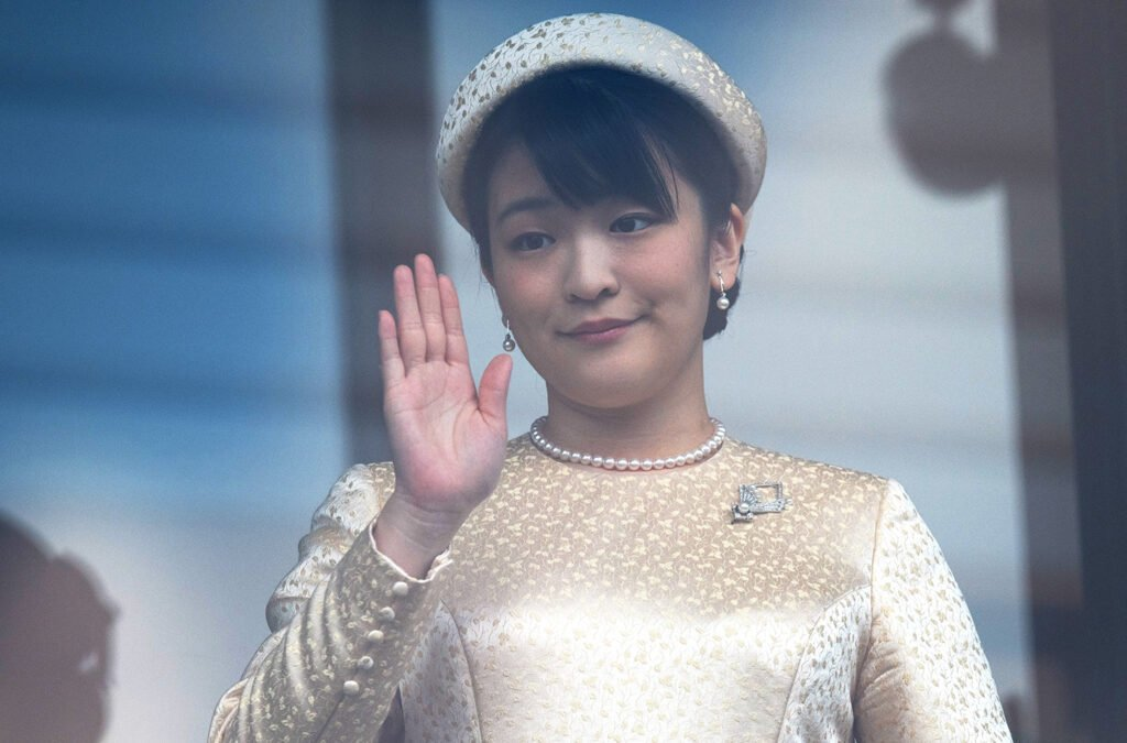 Princess Mako in a white dress and white hat, waving through a window.