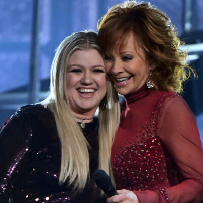 Kelly Clarkson and Reba McEntire hugging after a performance together.