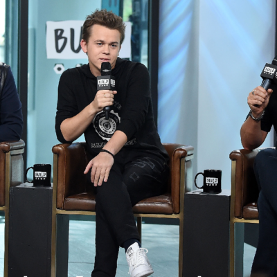 Rob Lowe and his sons John and Matthew wear black tops and bottoms during an indoor event